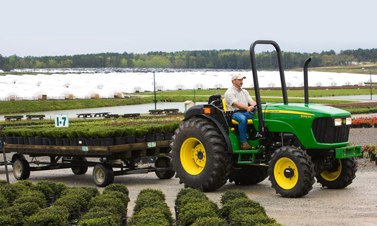 Man driving a John Deere specialty tractor with a trailer attached