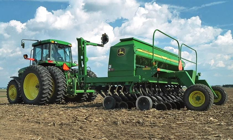 John Deere tractor with a Box Drill attachment in a harvested corn ...