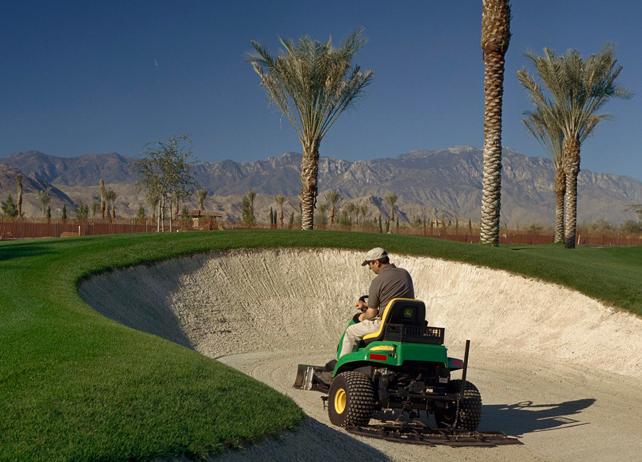 Groundskeeper using a John Deere bunker rake on a golf course