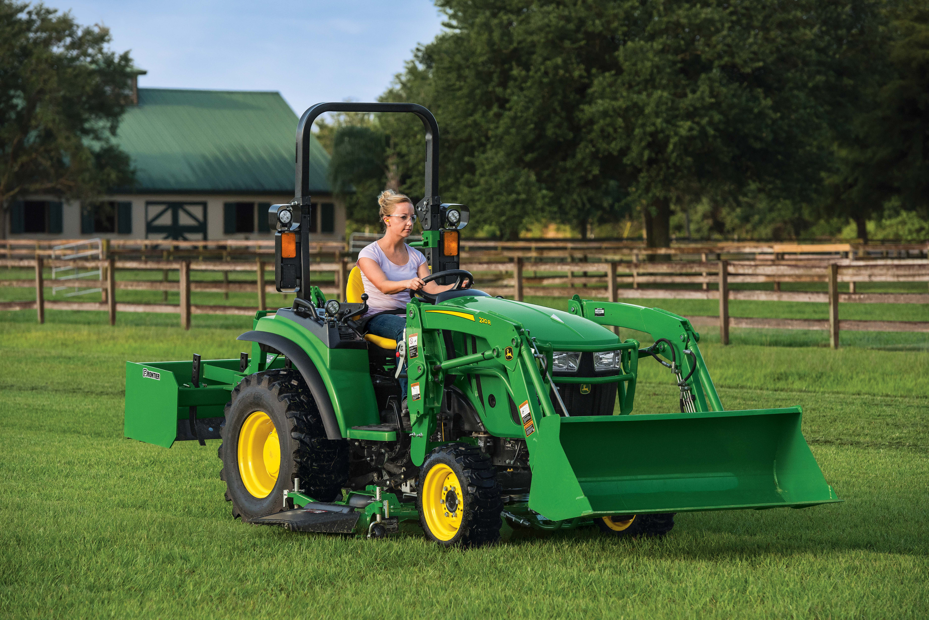 Woman using a John Deere 2R compact utility tractor on a farm